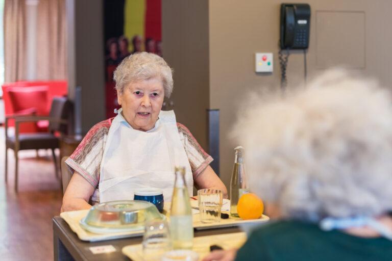 Une dame âgée de face et une dame de dos entrain de manger dans le réfectoire avec des plateaux repas