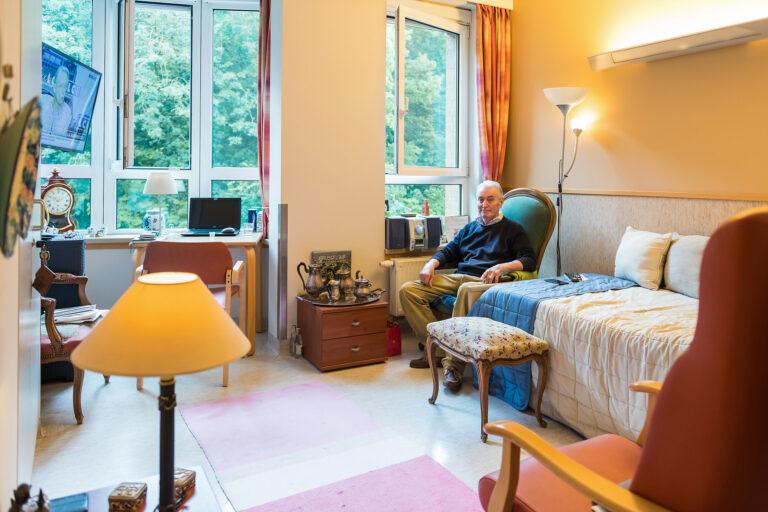 Un monsieur assis dans son fauteuil dans une chambre de Home